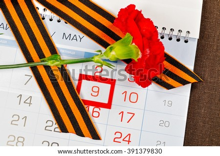 9 May concept. Victory Day greeting card - bright red carnation with George ribbon lying on the calendar with 9th May date  - stock photo