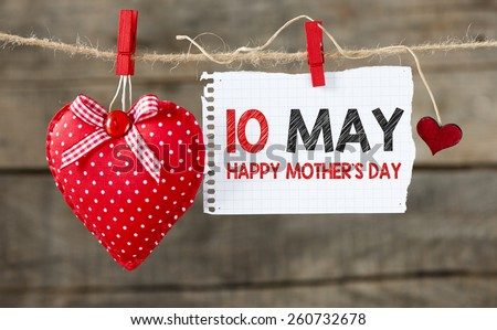 10 May Happy Mother's day message. Happy Mother's day message written on paper ,handling on rope with hearts. - stock photo