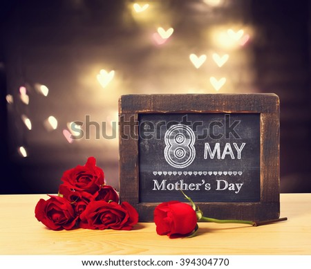 8 May Mothers day message on a small chalkboard with red roses  - stock photo