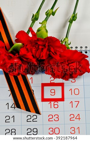 9 May postcard. St George ribbon and red carnations above the calendar with 9th May date - the day of victory in Great Patriotic War in Russia. 9 May concept.  - stock photo