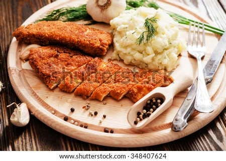meat with garnish , chicken cutlets in breadcrumbs , boiled mashed potatoes with herbs , garlic and spices on a wooden background - stock photo