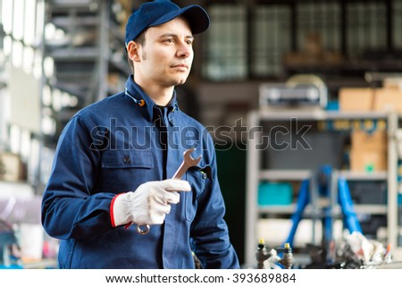 Mechanic at work in his garage - stock photo