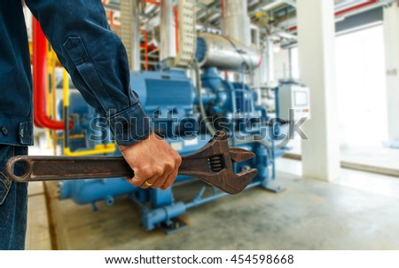 mechanic holding a large wrench industrial background.