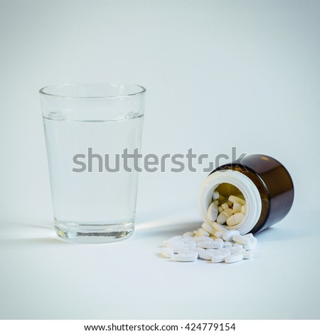 Medicines. Pills and glass of water - stock photo
