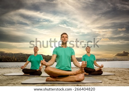 Meditating group in lotus position outdoor - stock photo