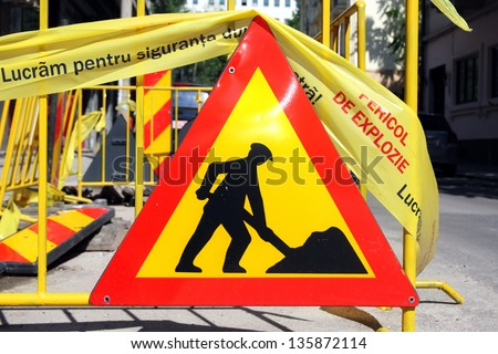 "'Men at work' road sign. The text on the yellow tape reads ""We work for your safety. Danger of explosion."" - stock photo"