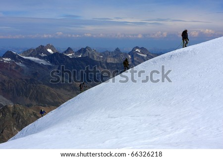 4 men climbing the top of the mountain