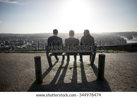 3 men unrecognizable sitting and relaxing on a bench in the sun enjoying a city scape view - stock photo