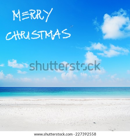 """merry christmas"" written in the sky over a turquoise shore - stock photo"