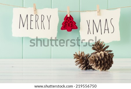 """Merry xmas"" and a felt tree hanging on a rope with clothespins. A robin egg blue wainscot as background and some pinecones on a white wooden table. Vintage Style. - stock photo"