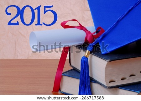 2015 message next to detail of blue cap and tassel and diploma tied with red ribbon, both resting on a stack of old books on a wooden desktop. Rough textured background that is neutral in color - stock photo