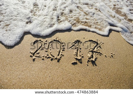 2017, message written in the sand at the beach background. Surf the waves on the sand