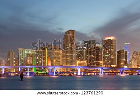 Miami Florida sunset over downtown illuminated business and luxury residential buildings, hotels and Biscayne Bay bridge.Night Cityscape of World famous travel location. - stock photo