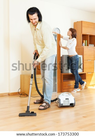 middle-aged couple doing housework together in home - stock photo