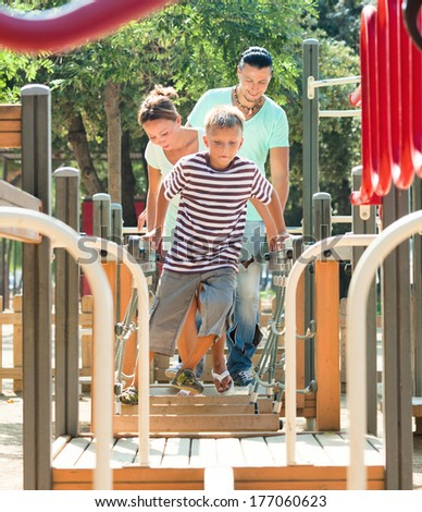 Middle-aged  couple together with teenager overcomes the obstacle course on the playground