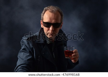 middle-aged man in sunglasses with glass of whiskey