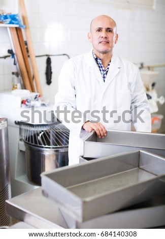 Middle aged positive worker standing near the table in food manufacture