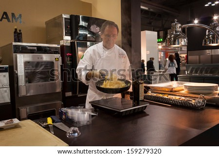 MILAN, ITALY - OCTOBER 18: A cook prepares food at Host 2013, international exhibition of the hospitality industry on OCTOBER 18, 2013 in Milan. - stock photo