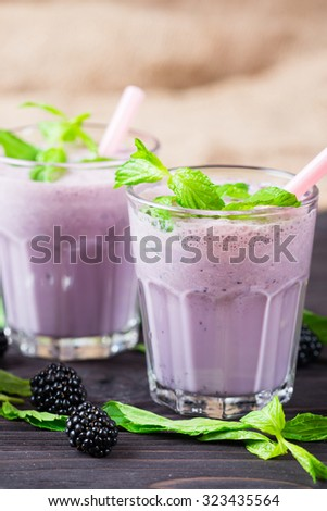 Milk cocktail with blackberry and mint in glass on a rustic wooden background