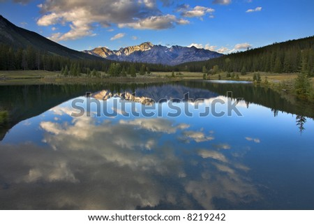 Mirror reflection of the sky and clouds in water of mountain northern lake