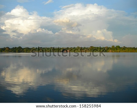 Mirrored sky and forest line on the Rio Negro in the Amazon River basin, Brazil, South America          - stock photo