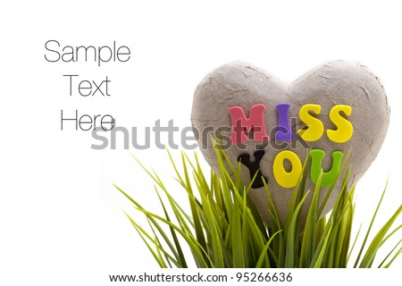 'Miss you' sentiment spelled out with letters on broken heart made of paper, isolated on white background - stock photo