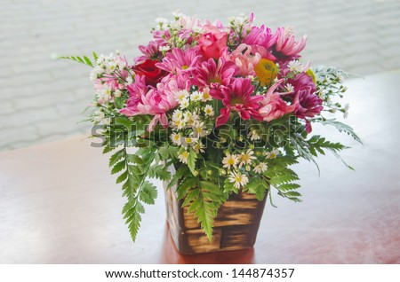 mix  of fresh  flowers in vase  on wooden table