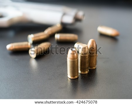 11mm bullets and short gun on black background. (selective focus) - stock photo