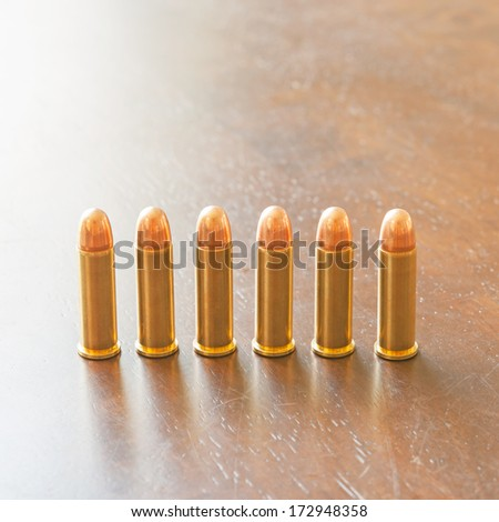9mm bullets on table - stock photo