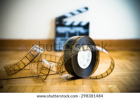 35 mm cinema film reel and out of focus movie clapper board in background on wooden floor - stock photo