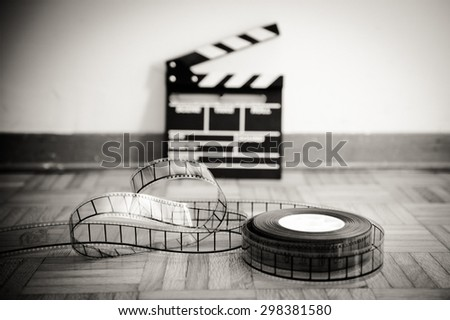 35 mm cinema film reel and out of focus movie clapper board in background on wooden floor in vintage black and white - stock photo