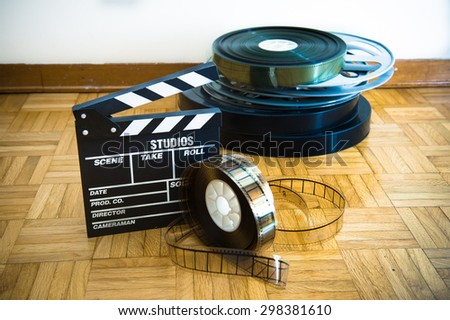 35 mm cinema movie clapper board and film reels in background on wooden floor - stock photo