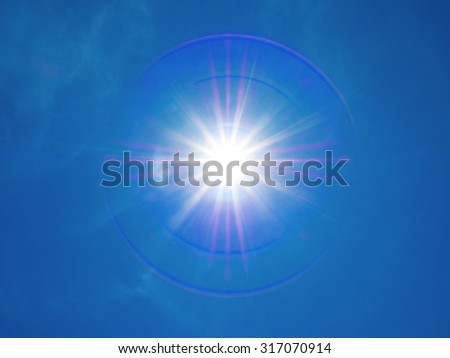 12mm lens flare of the sun on blue sky with little cloud
