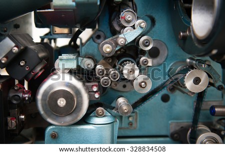 35 mm movie cinema projector detail with spool and film running, close up in selective focus - stock photo