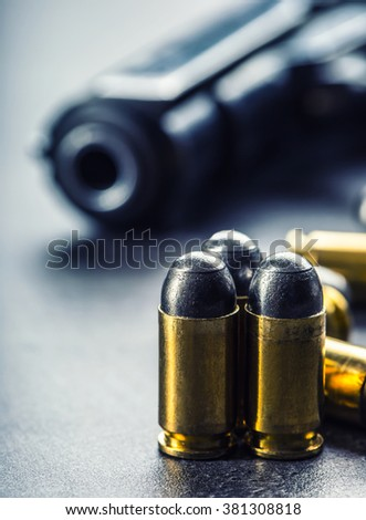 9 mm pistol gun and bullets strewn on the table. - stock photo