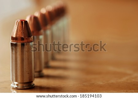 9mm polymer tipped bullets (used for concealed carry guns) on wood background.  Macro with shallow dof and copy space.  Selective focus limited to first bullet.
