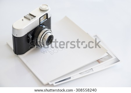 35mm vintage photocamera on wedding book with print - stock photo