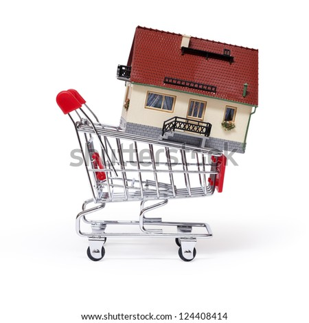 Model of the house in shopping cart on white background.