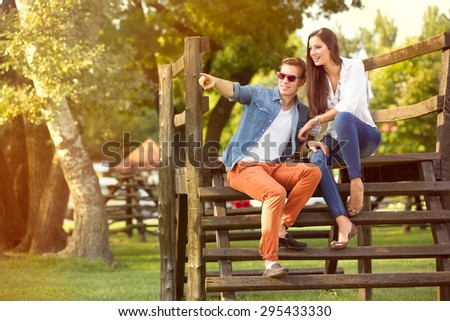 Modern fashion couple of young lovers in the park - stock photo