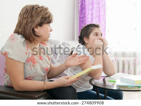 Mom and daughter doing homework at home.  - stock photo