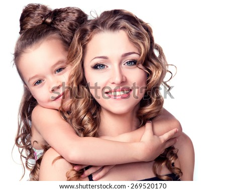 Mom and Daughter Hug. Daughter hugging her mother from behind while both are smiling. Happy portrait of beautiful young mother with little pretty daughter - isolated on white. - stock photo