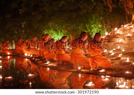 monks sitting meditate with many candle in Thai temple at night , Chiangmai ,Thailand, soft focus - stock photo