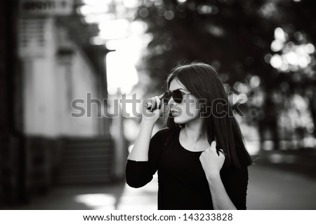 monochrome outside portrait of a young dark hair woman wearing sunglasses - stock photo