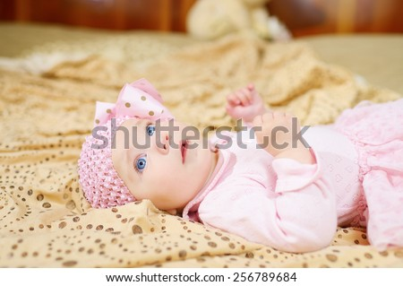 6 month blue-eyed baby girl in a pink dress and hat with a bow on a beige blanket with a pattern of circles - stock photo