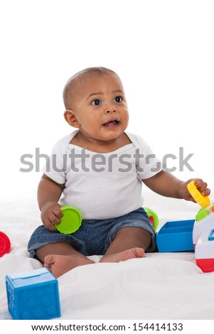 7-month old african american baby  boy playing with toys on white background