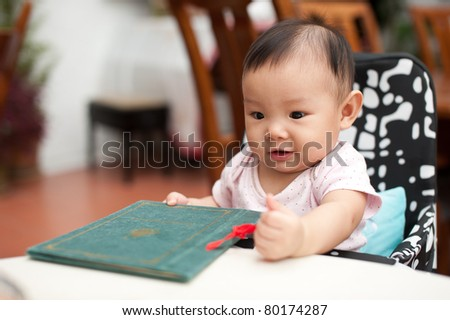 7 month old Asian baby girl, holding the menu, about to order her meal