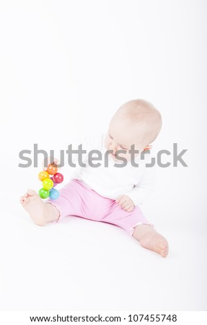 8 month old baby girl playing with her toy.  studio shot on a white background - stock photo