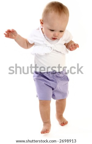 14 month old baby girl walking over white background.