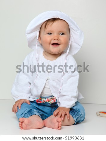 7 month old baby sitting with toy dressed in jeans and jumper