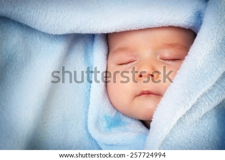 3 month old baby sleeping on blue blanket - stock photo